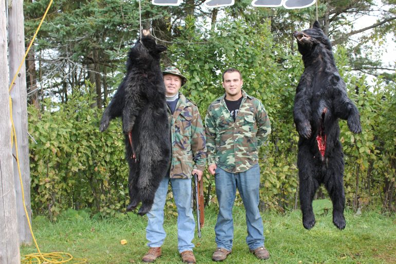 Father and son bear hunting partners with trophy bear at Foggy Mountain Guide Service