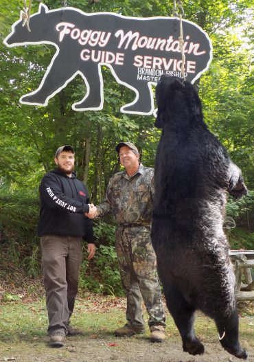 Brandon Bishop owner of Foggy Mountain congratulating a successful bear hunter